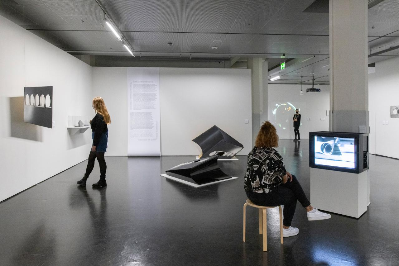 Three women in the exhibition. The woman on the left is looking at a sculpture that is hung on the wall, the woman on the right is watching a film on a TV, in the middle are abstract figures, on the back wall is a wallpaper roll with text on it.