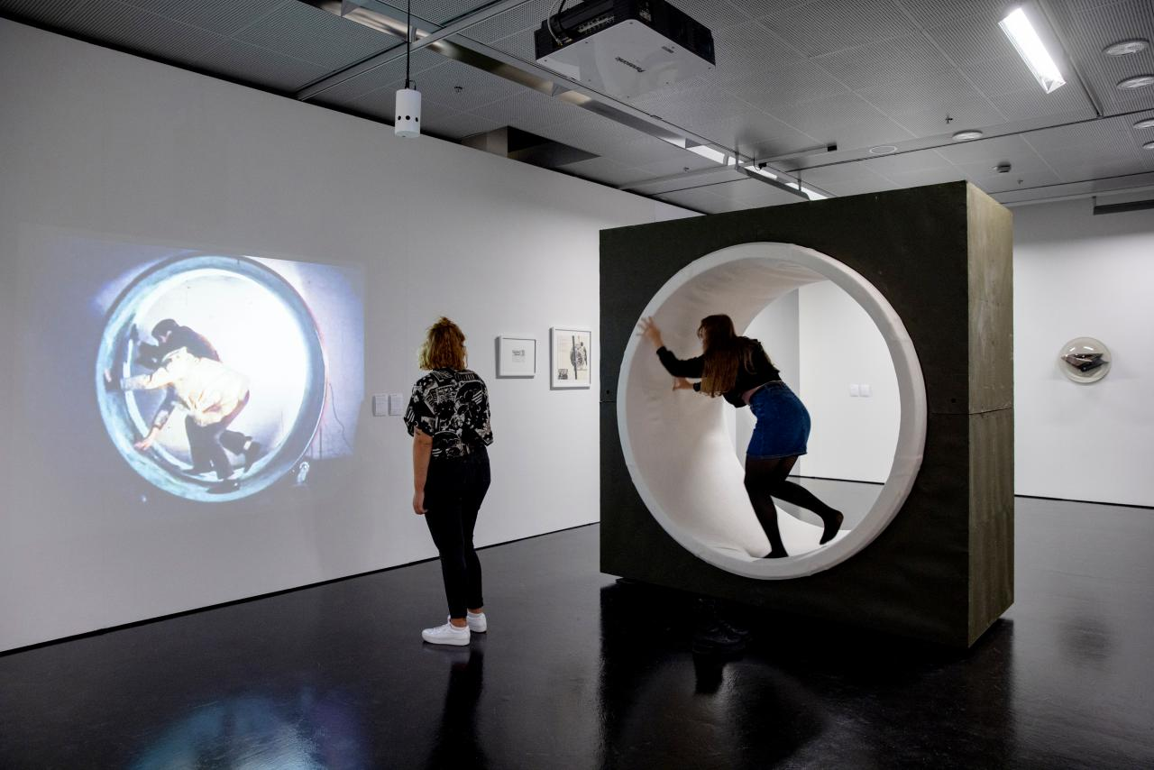 Two young women are in the exhibition room. One is watching a projection of an artistic film on a wall and the other is in a tredmill kind of role.