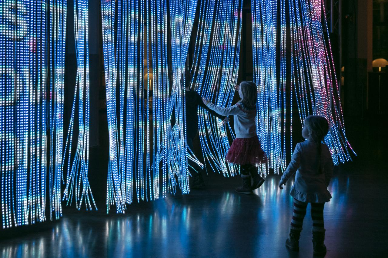 Children step through a curtain of light sticks on which many bright colours and lettering are projected.