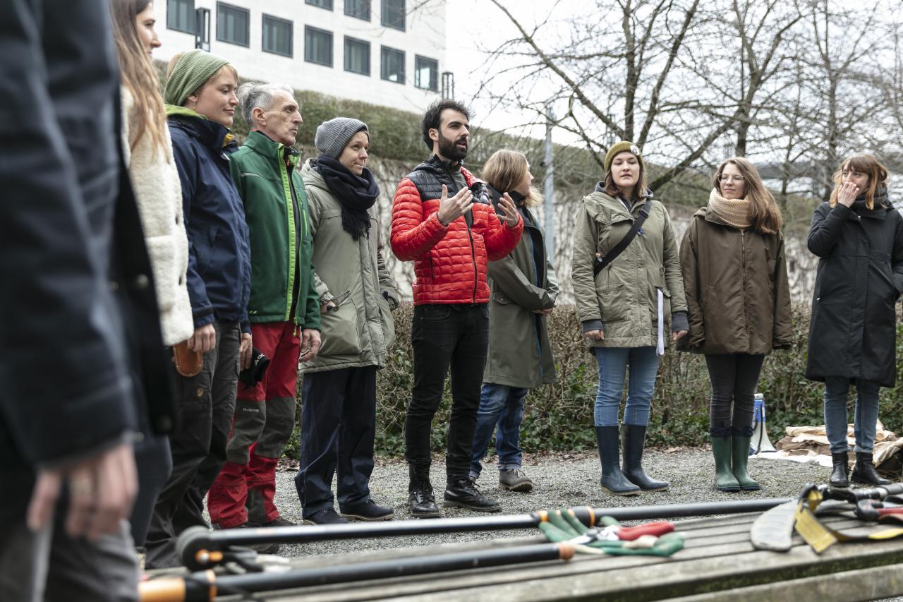 Eine Gruppe von Menschen stehen vor Gartenwerkzeugen im Rahmen des Baumschnitt-Kurses vom ZKM.