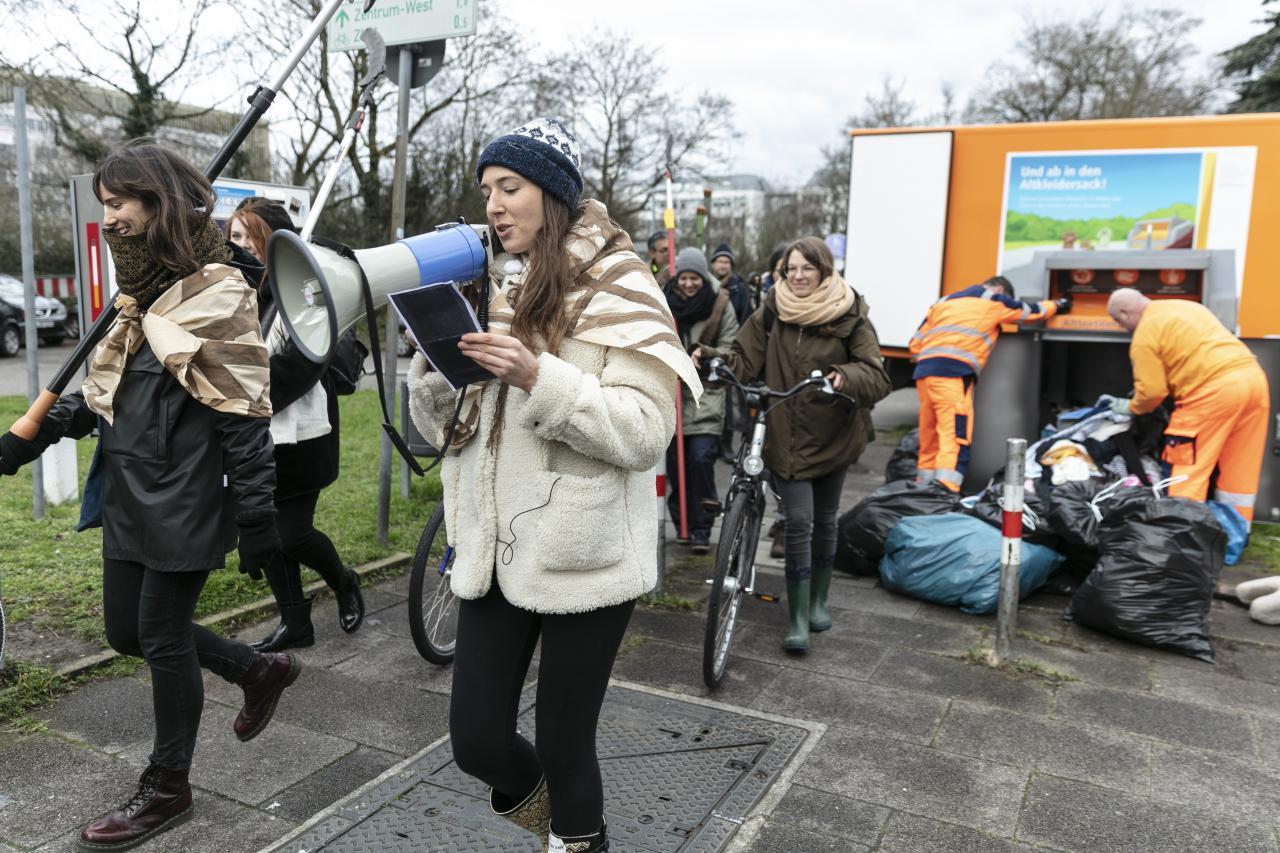 Eine Gruppe von Menschen gehen in einer Prozession mit Gartenwerkzeugen, Fahrrädern und Megafon.