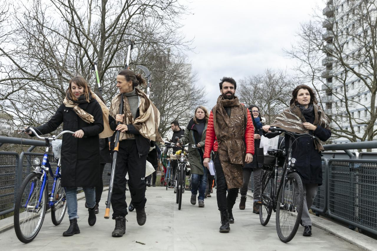 Eine Gruppe von Menschen gehen in einer Prozession mit Fahrrädern.