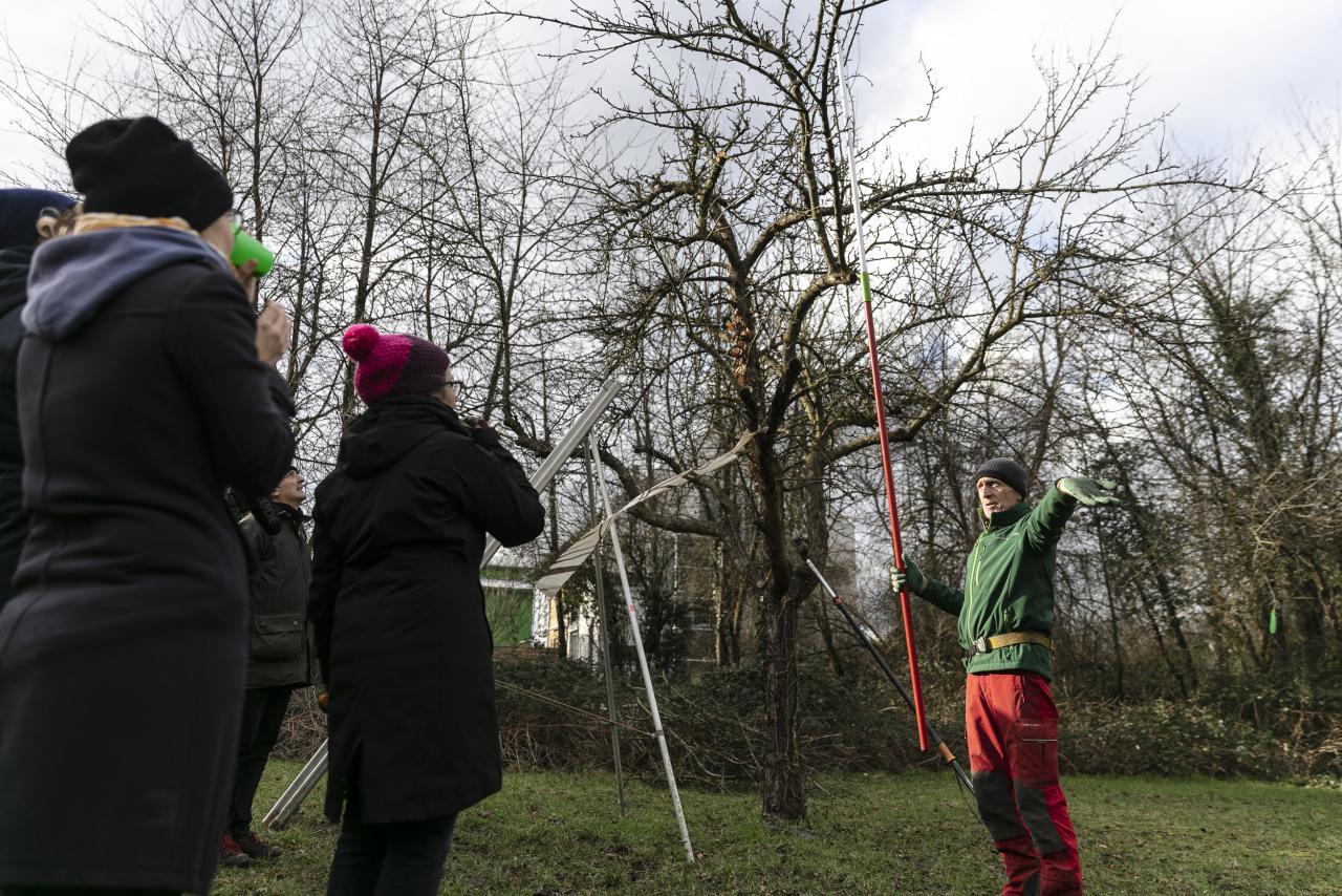 Ein Mann in Outdoor-Kleidung spricht vor eine Baum zu einer Gruppe.