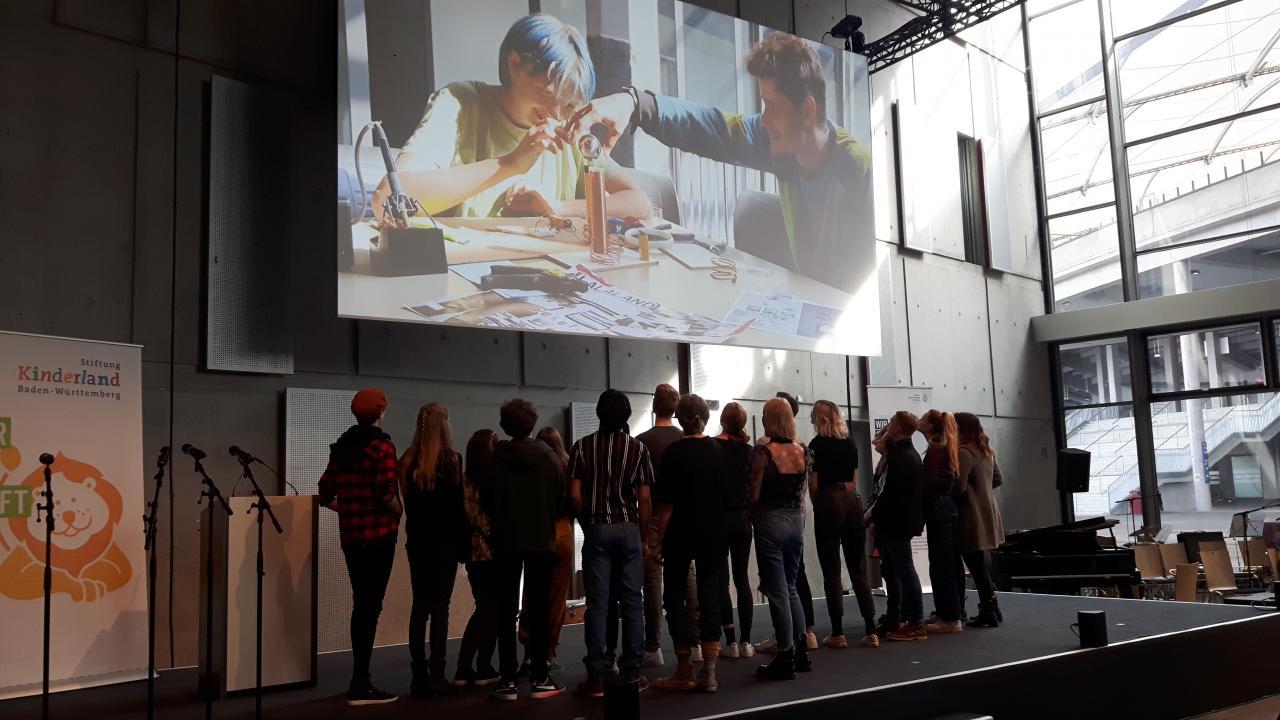 Eine Gruppe von Schülern stehen unter einer Projektion im Rahmen des Projektes »Kulturakademie« am ZKM.