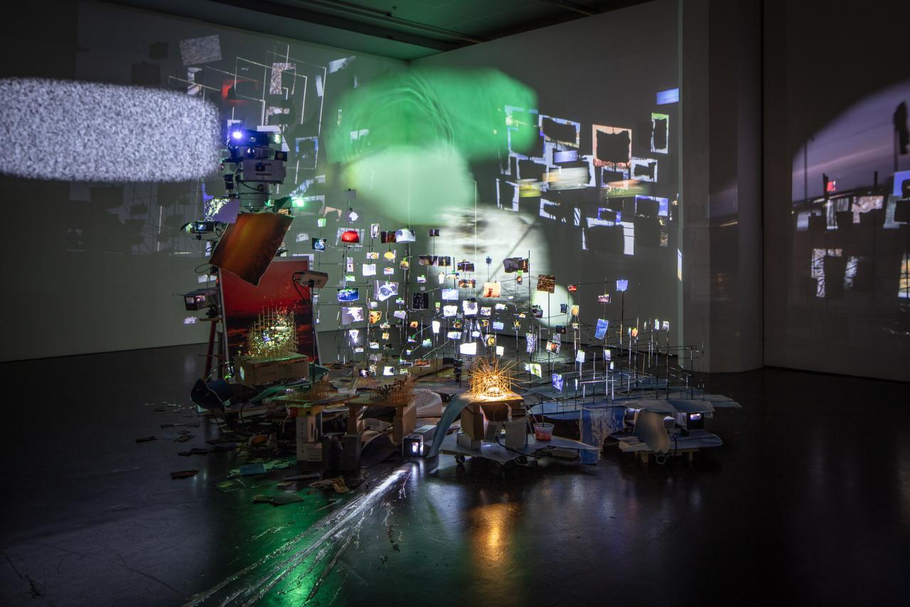 Zu sehen ist eine filigrane Installation aus dünnen Stäben, an denen kleine Papierstückchen befestigt sind. Auf jedem Stückchen Papier ist eine Lichtprojektion zu sehen. Die Installation steht in einem dunklen Raum. Auf den Wänden des Raums sind ebenfalls