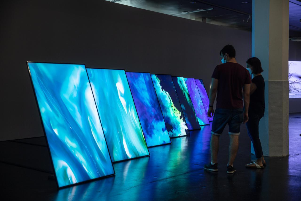 Zu sehen sind sieben große hochkant Flachbildschirme. Die Bildschirme zeigen Luftaufnahmen des Meers.