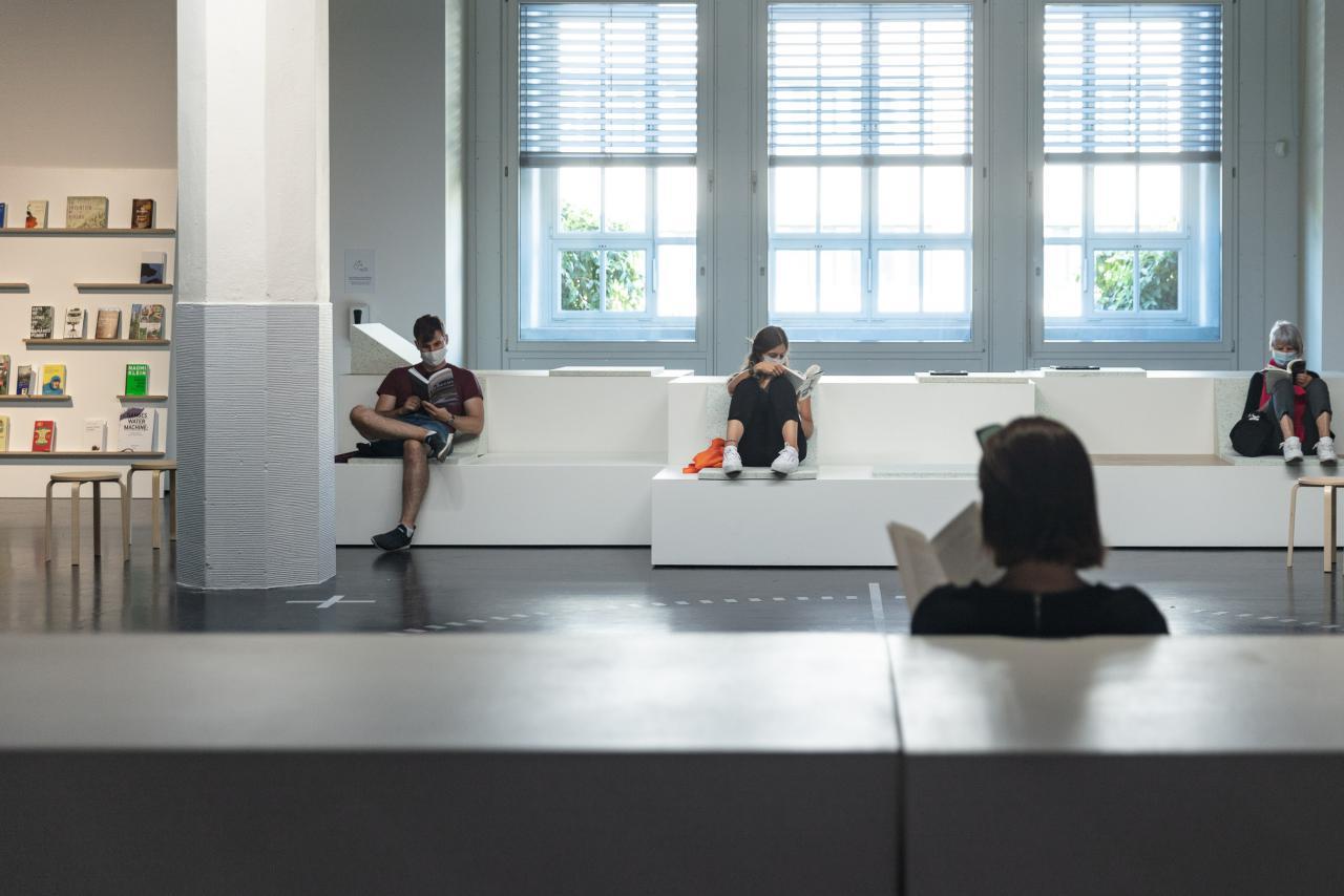 Zu sehen ist eine Sitzecke, auf der mehrere Menschen Buch lesend sitzen.