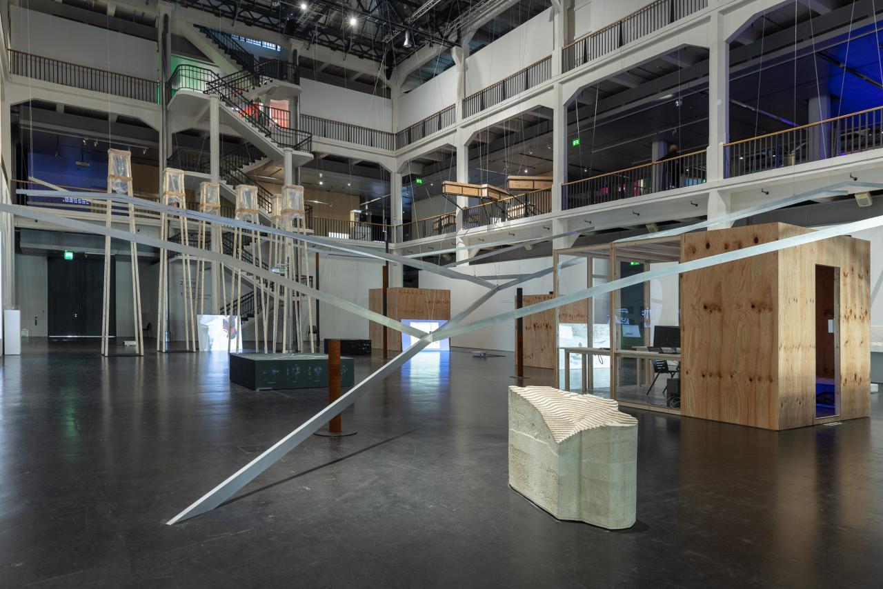 Blick in den Lichthof und auf die Installation, die sich durch den ganzen Lichthof erstreckt. Ein Metallgerüst deutet die Topologie des Strengbach Observatorium an. Im Raum verteilt sind Bildschirme mit Videos zu sehen.