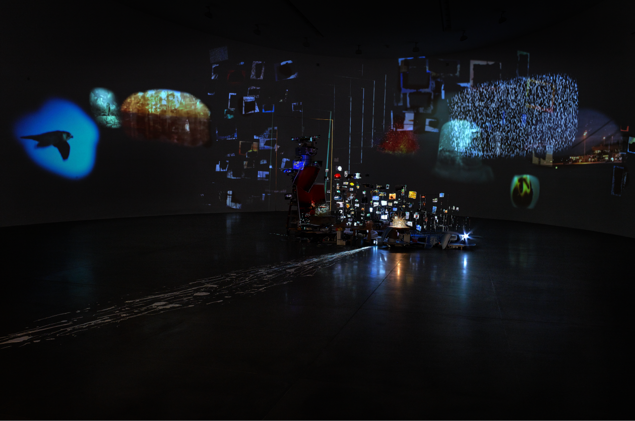 Photo of a dark exhibition room with luminous reflections.