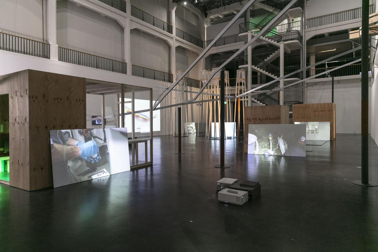 View into a large hall with a scaffolding and white walls on which videos are shown.