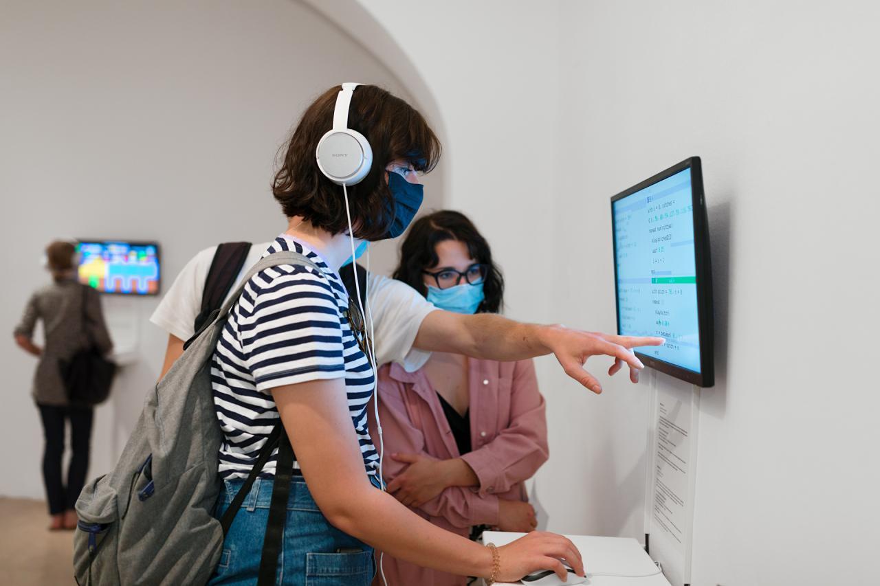 Eine Frau zeigt auf einen Bildschirm. Mit der anderen Hand hält sie eine Computermaus. Sie trägt Kopfhörer.