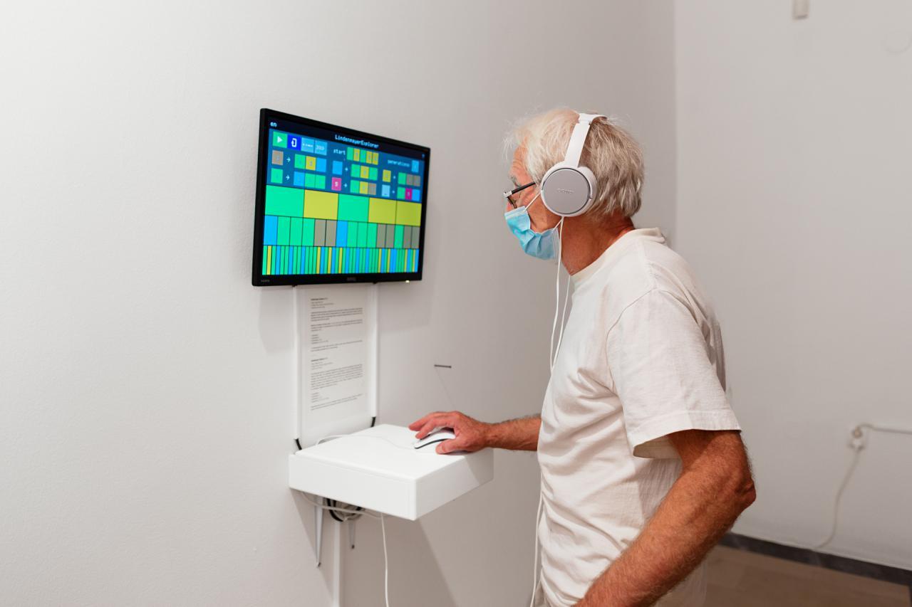 Ein Mann steht vor einem Bildschirm und steuert diesen per Computermaus.