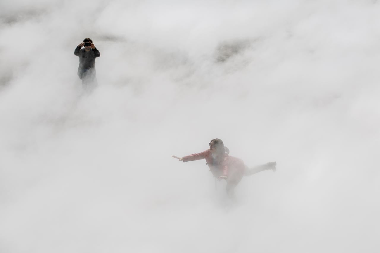 Zu sehen ist eine auf einem Bein balancierende Frau mit ausgestreckten Armen, halb versteckt im Nebel.