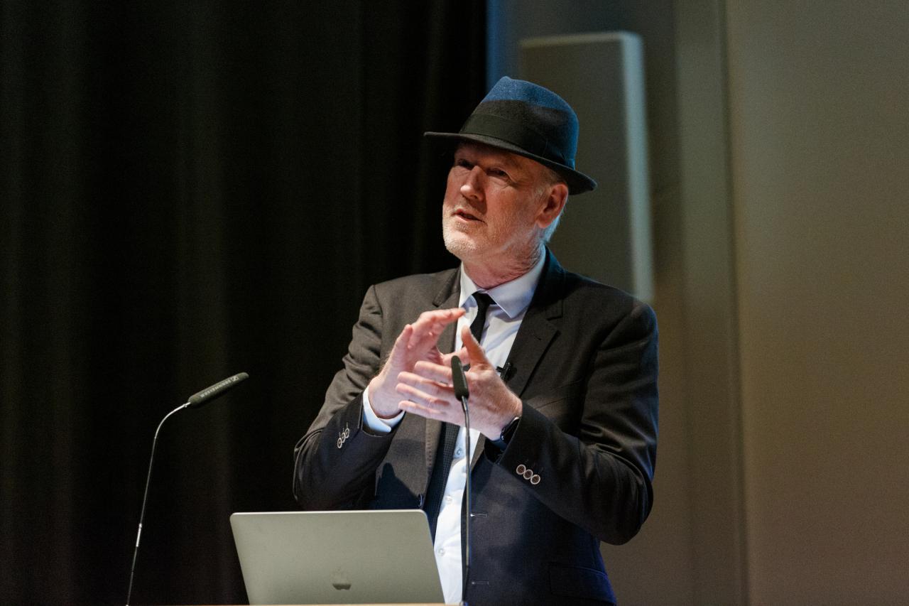 Zu sehen ist Thomas Paul, Medienkünstler und Professor in Anzug mit Hut, wie er hinter einem Rednerpult mit Laptop steht und gestikuliert.