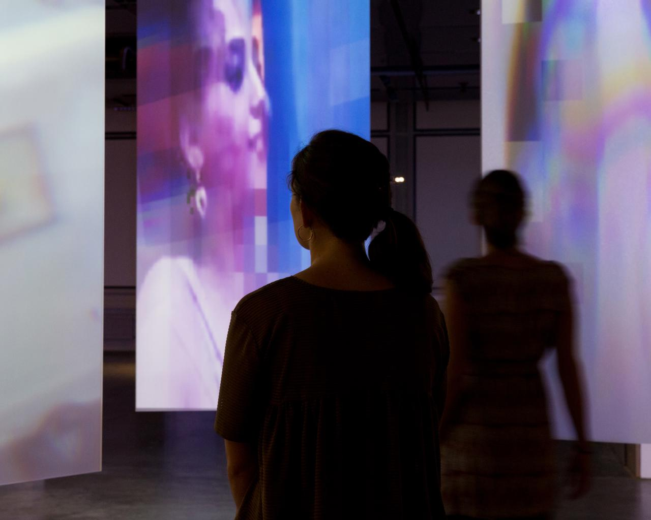 The silhouettes of two visitors in front of filmed screens