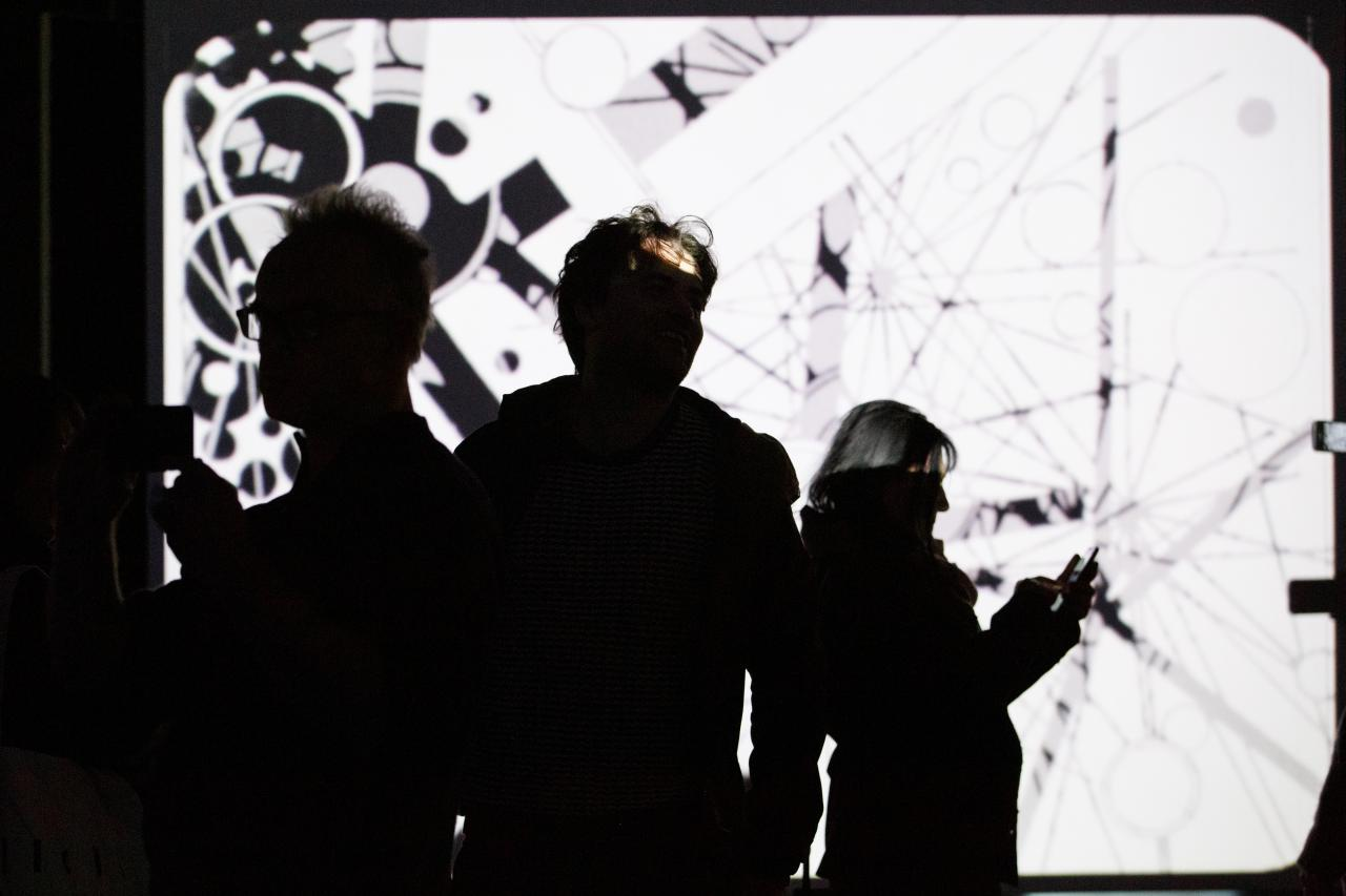 Foto von Menschen vor einer Leinwand mit einem abstrakten Video in Schwarz-Weiß – Eine Impression der Ausstellung »bauhaus.film.expanded« am ZKM Karlsruhe.