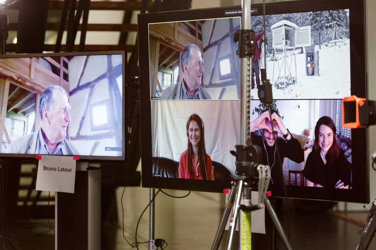 Two large monitors on which four people, among them Bruno Latour, can be seen via video call.