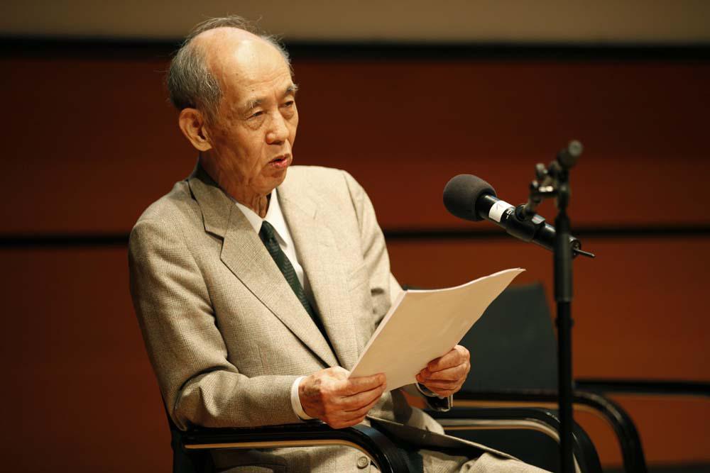 Hiroshi Kawano bei seinem Vortrag. Er trägt einen hellen Anzug, in den Händen hält er sein Manuskript.