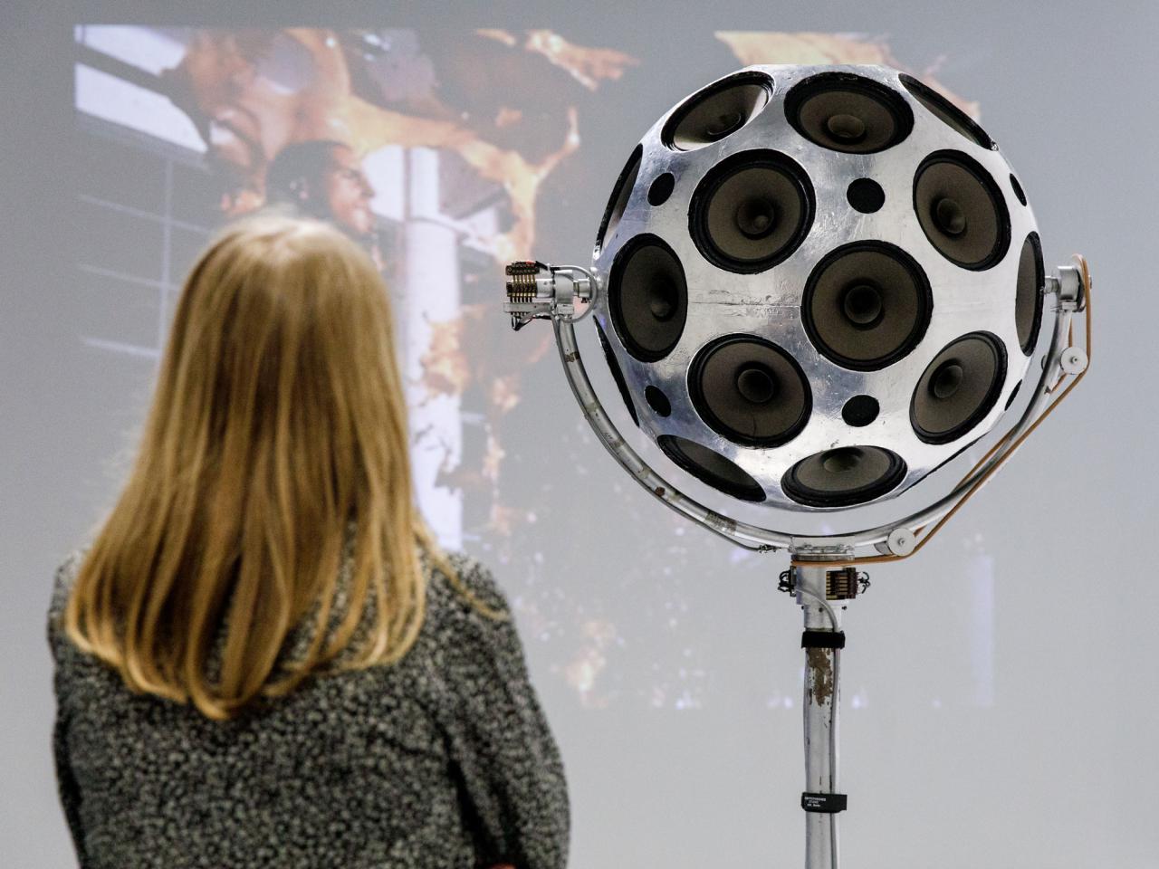 Eine Frau steht vor einer silbernen Kugel aus Lautsprechern