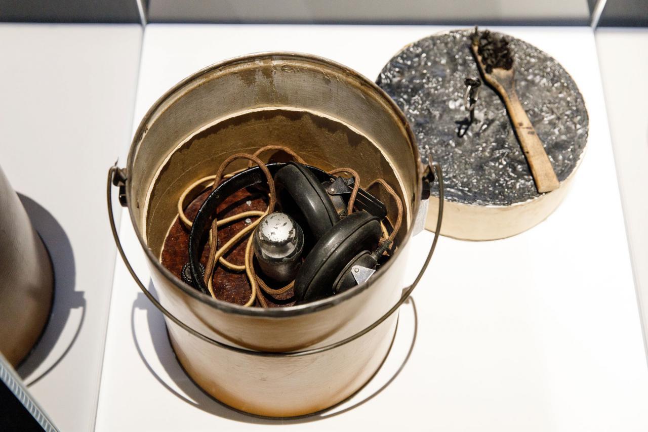Metallener Eimer mit Kopfhörern und Kabeln