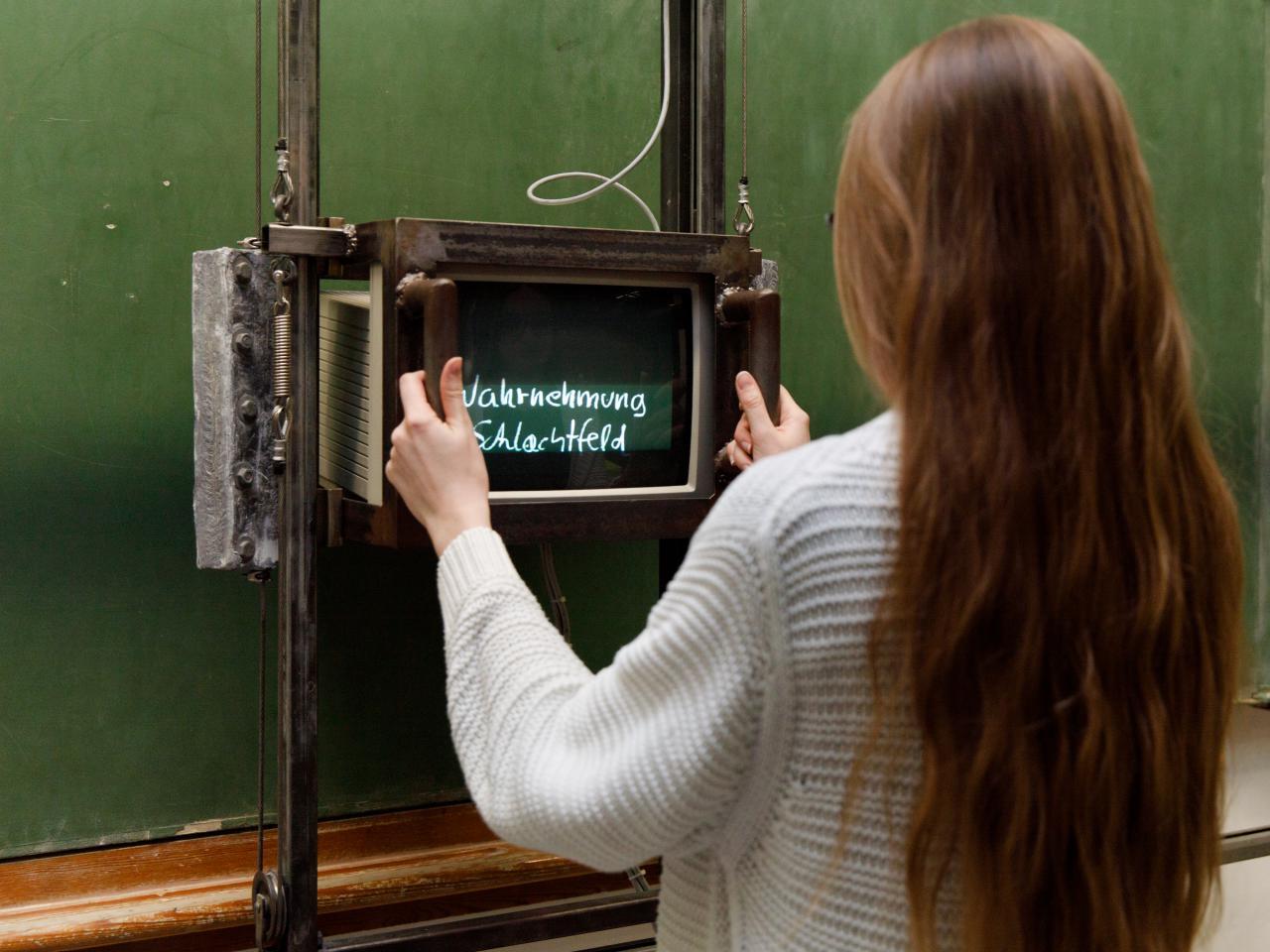 Besucherin vor Fietzeks »Tafel«, eine leere grüne Schultafel, auf der mit Hilfe eines Monitors zuvor unsichtbare Texte auftauchen.