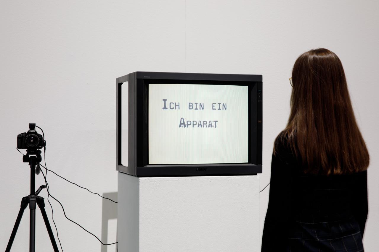 Links eine Fotokamera. Mittig auf augenhöhe ein Fernsehbildschirm. Auf dem Display die Aufschrift: »Ich bin ein Apparat«. rechts steht eine braunhaarige Frau, den Bildschirm betrachtend, den Rücken zum Betrachter.