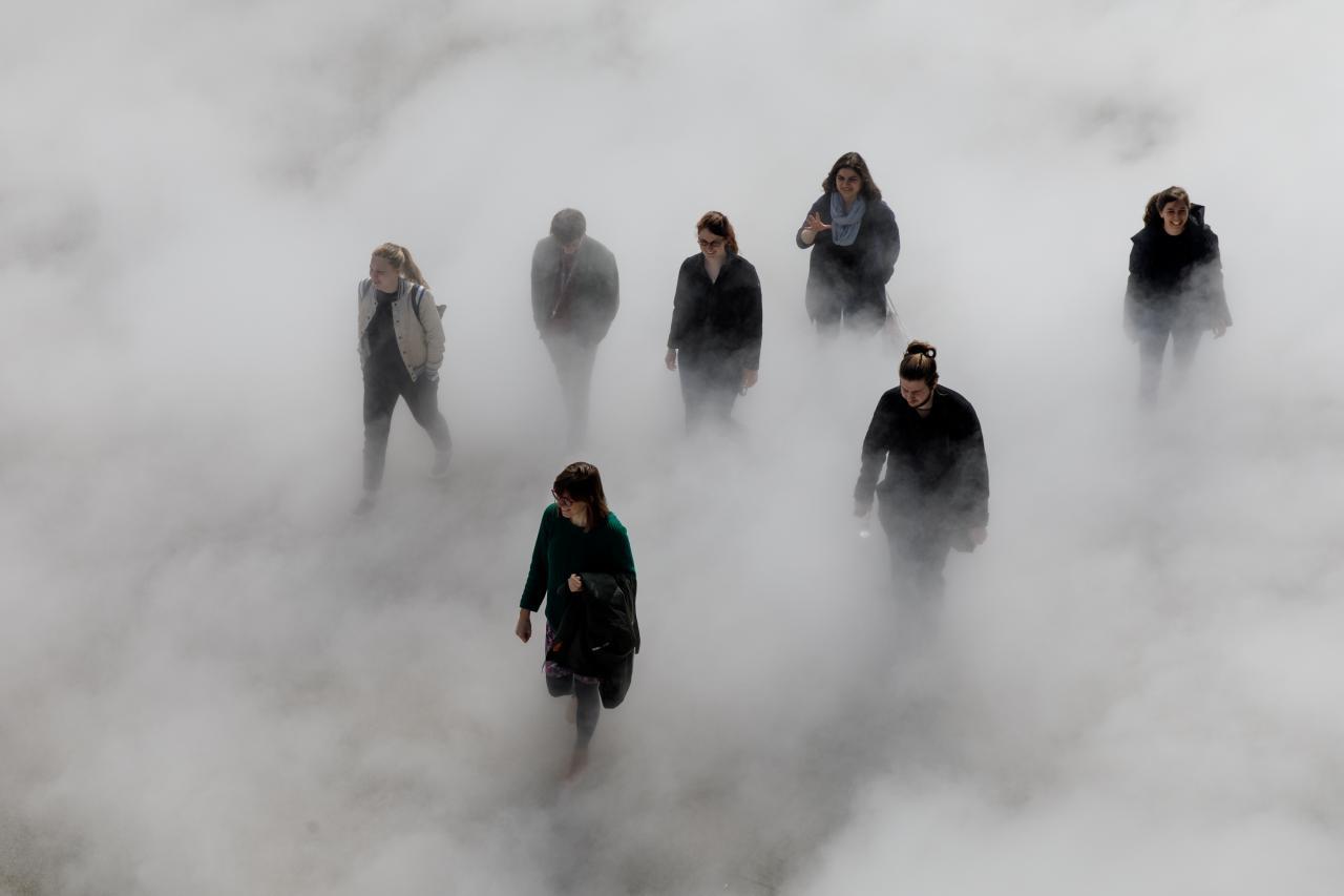 Das Foto zeigt sieben lachende Menschen, die über den Platz der Menschenrechte laufen und zum Teil vom Nebel verdeckt sind.