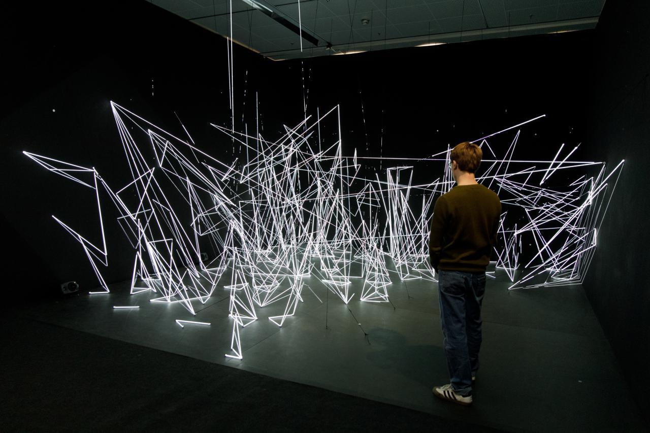 Eine Installation aus weißen, beleuchteten Nylonfäden in geometrischen Formen.