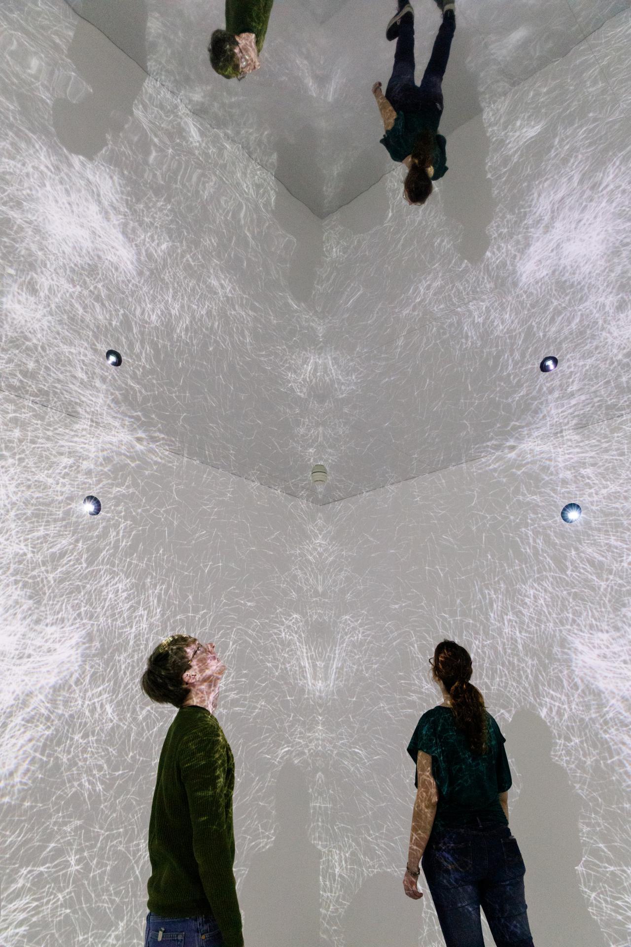 Besucher in einem Raum mit Videoprojektionen an Wänden und Decke und einem verspiegeltem Boden.