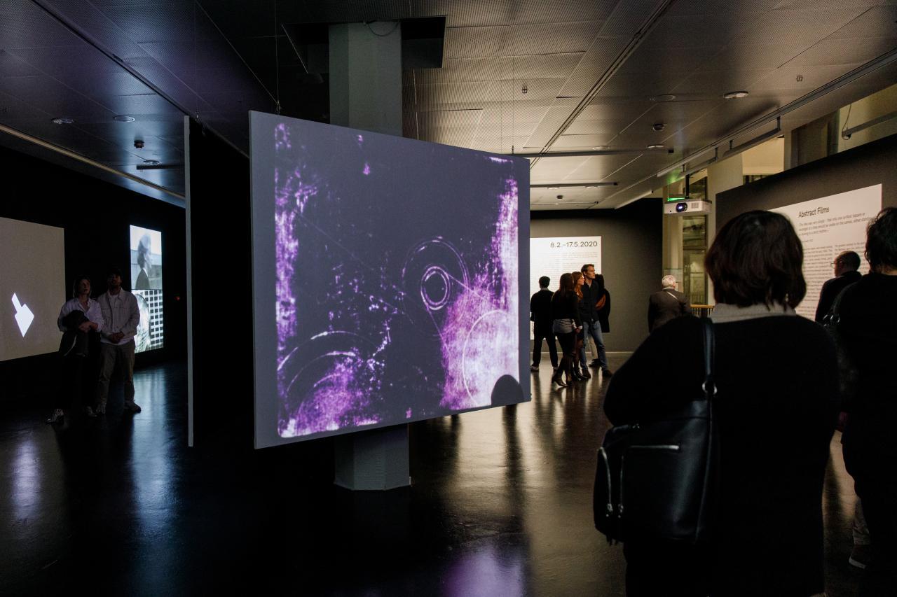 Foto von Menschen vor einer Leinwand mit einem abstrakten Video in Lila – Eine Impression der Ausstellung »bauhaus.film.expanded« am ZKM Karlsruhe.