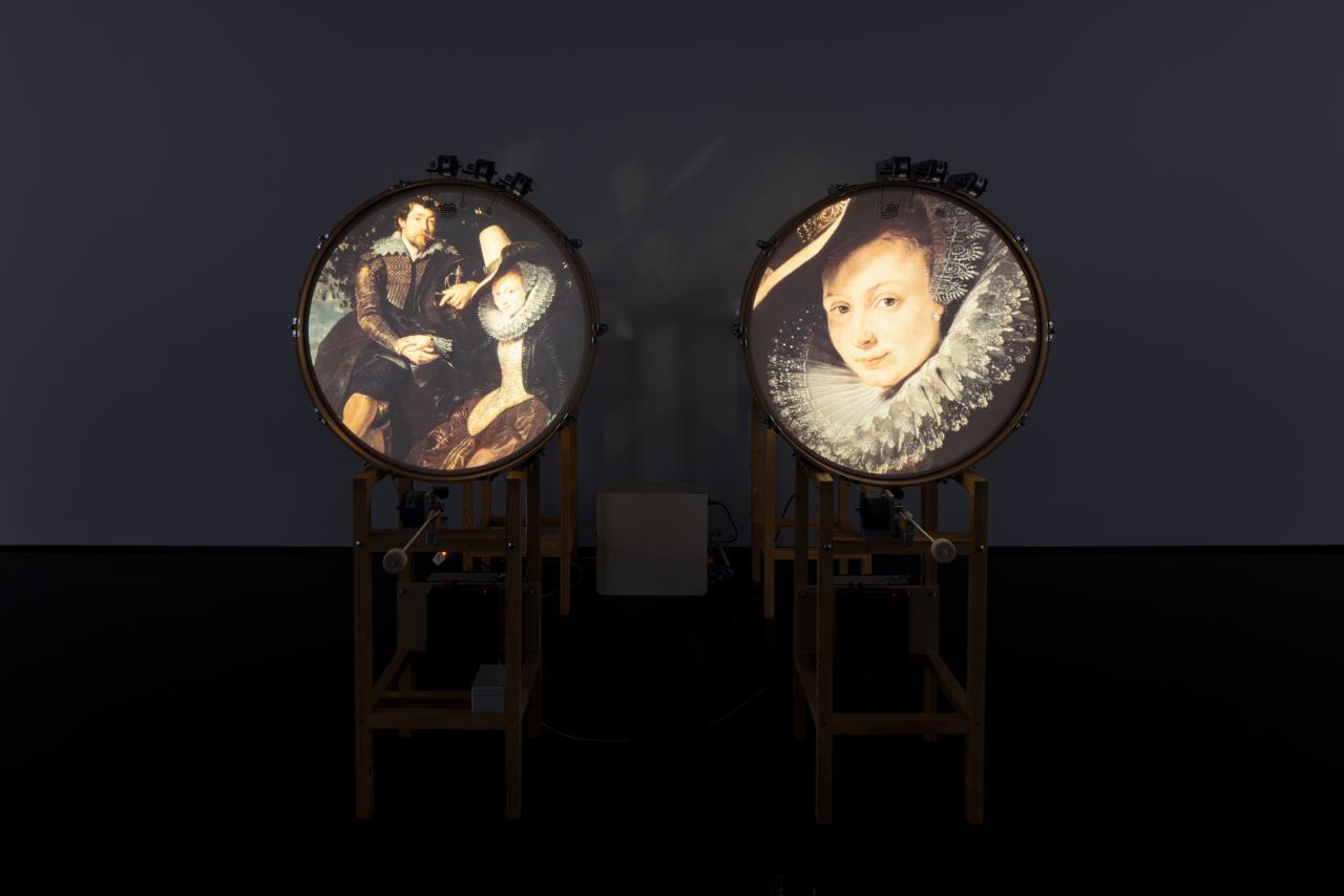 Zu sehen sind zwei stehende Trommeln, welche jeweils ein Bild auf der runden Fläche zeigen. Links ein altertümliches Ehepaar und rechts das Porträt einer Frau.
