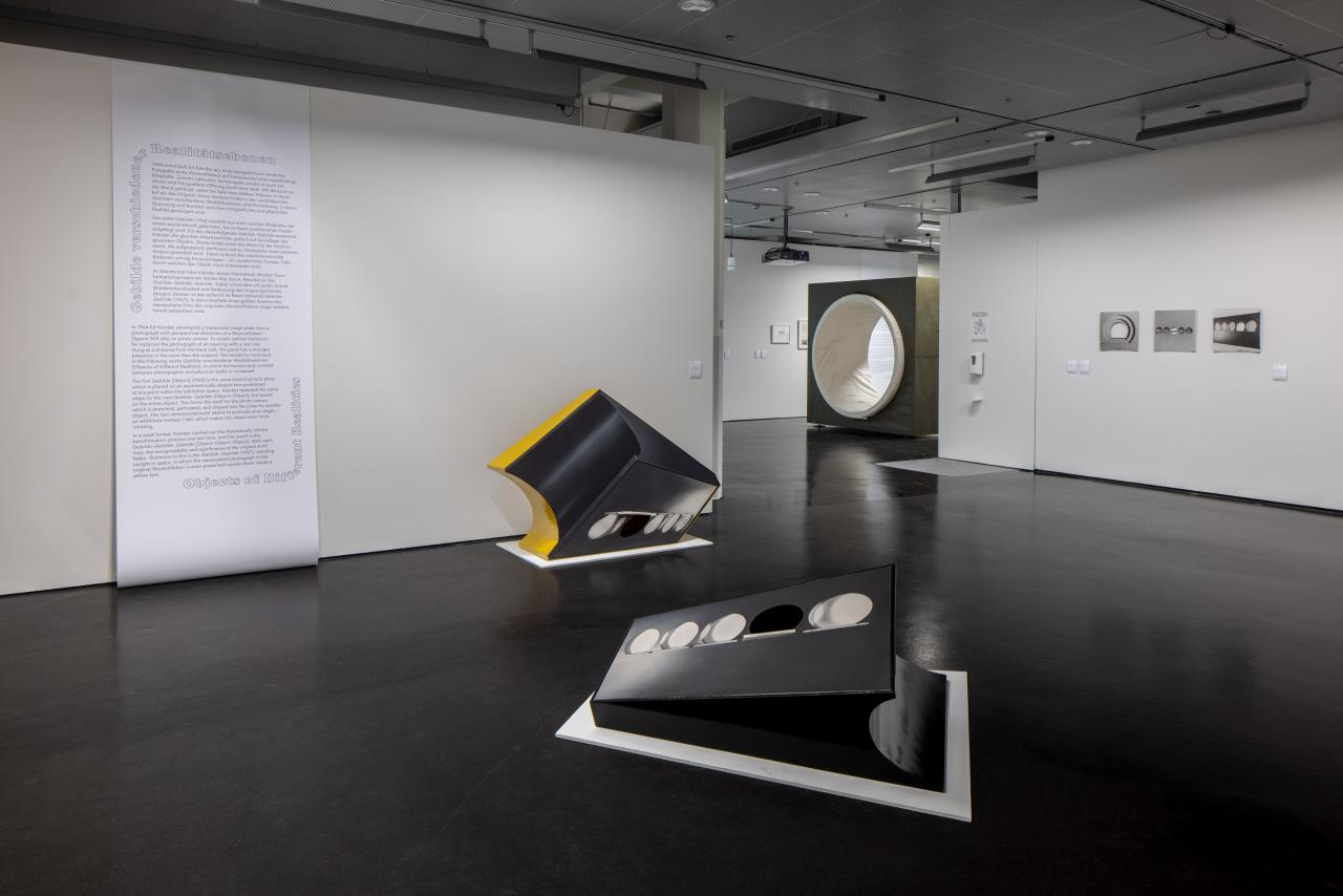 In the exhibition space, two sculptural works can be seen in the foreground. In the background, text is written on the wall and other works can be seen.
