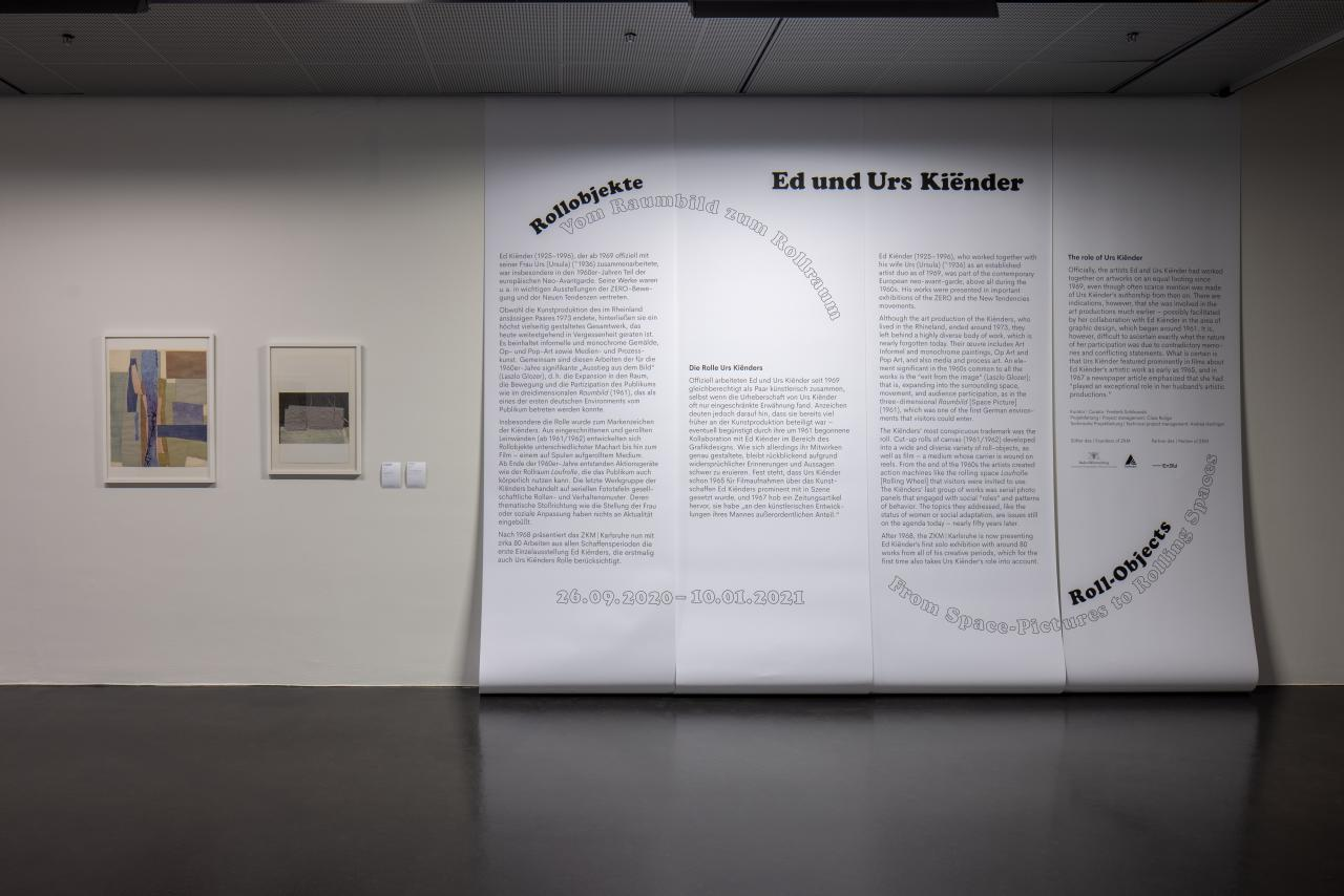 In addition to large-scale mounted exhibition text on the wall, the picture shows two other works hung on the wall and framed.