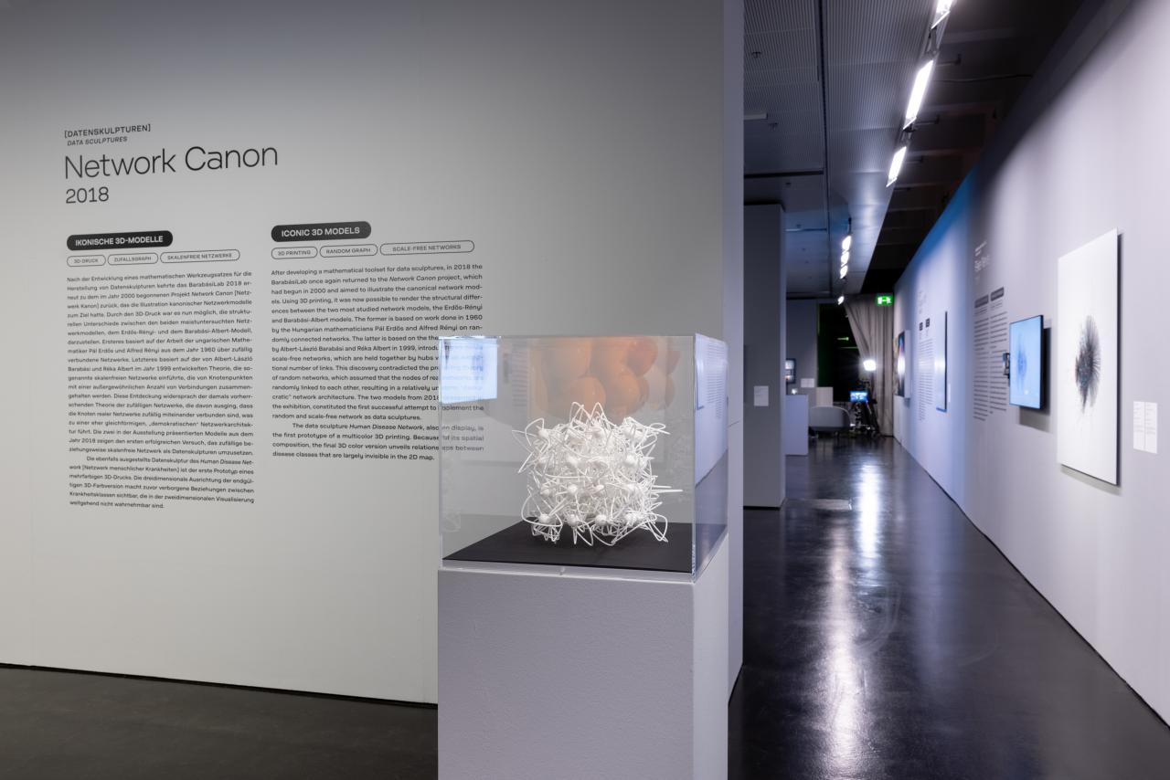 A showroom with a white 3D network model in a glass box.