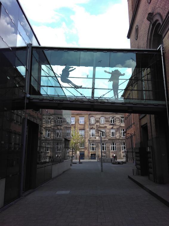 Das Bild zeigt den Blick in eine Gasse mit Sandsteinhäusern. Zwischen den Häusern sieht man eine schräg verlaufende Brücke, die mit Glas abgedeckt wurde. Auf der Brücke springen zwei Personen, die man durch das Glas sillhouettenhaft sieht..