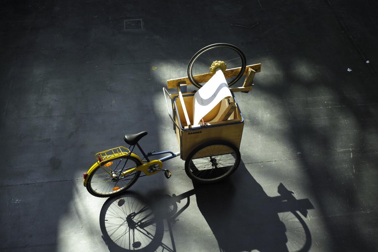 Das Lesefahrrad ist auf einem selbstgebauten Lastenfahrrad aufgebaut. Einige Holzreste sind hinzugefügt, einige Schrauben, ein Rad von einem kaputten Fahrrad, allgemeine Reste aus dem Lebensprozess, Gegenstände, die einst Teil von etwas Größerem waren.