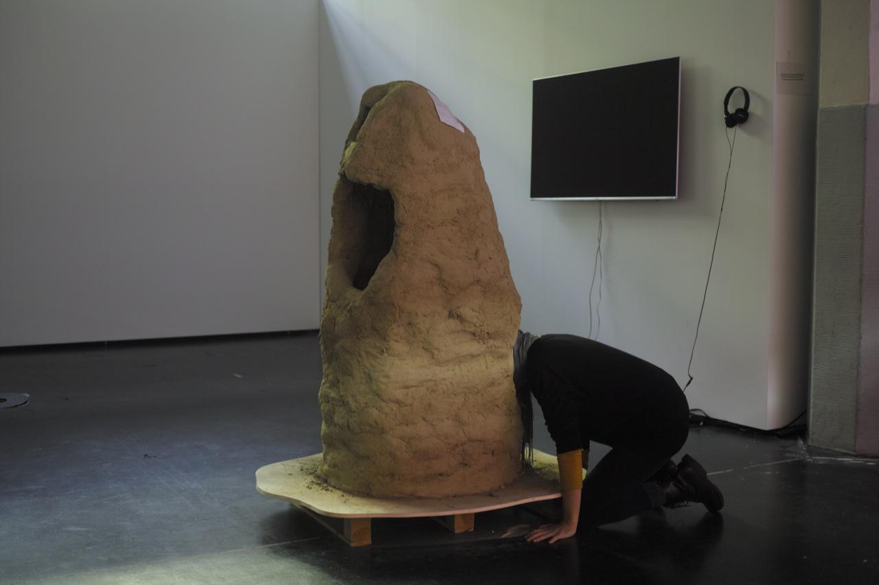 Diese Skulptur ist aus Lehm gefertigt (und von Lukas Marstaller und Oliver Boulam gebaut) und sieht einem Termitenhügel ein wenig ähnlich. Sie hat zwei Öffnungen, gerade groß genug, um den Kopf hineinstecken zu können.