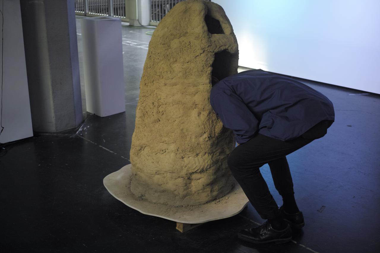 This sculpture is made of loam (and built by Lukas Marstaller and Oliver Boulam) looks a bit similar to a termite hill. It has two openings, just large enough to put your head inside.