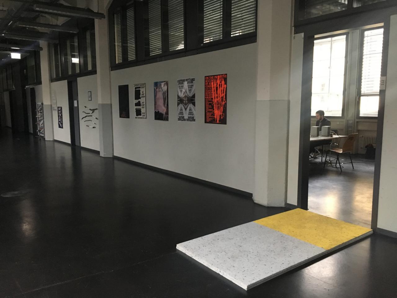 Vor dem Eingang des Seminarraumes des Critical Zones Forschungsseminars an der Staatlichen Hochschule für Gestaltung Karlsruhe (HfG) befindet sich eine Schaumstoffmappe auf dem Boden als Test für alle SeminarteilnehmerInnen.