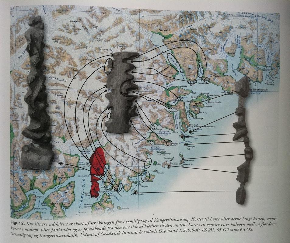 The photo shows the cartography of Greenland. On it lie various elongated wooden sculptures