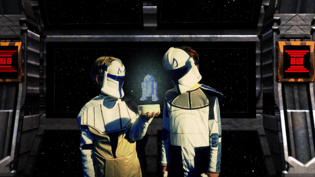 Zwei verkleidete Kinder stehen frontal zur Kamera und tragen weiße Roboter-Masken. Zwischen ihnen wurde eine Hollografie mit digitalen Mitteln eingefügt, auf die die beiden ihre Blicke gerichtet haben.