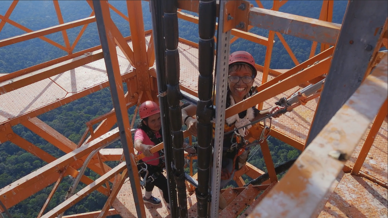 You can see two women with helmets on their heads, grinning as they climb up a steel scaffolding.