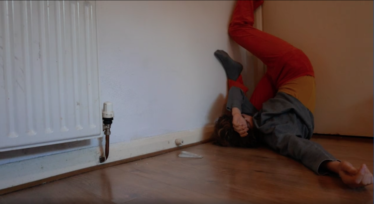 The image shows a person lying on the floor and moving along the wall with his legs.