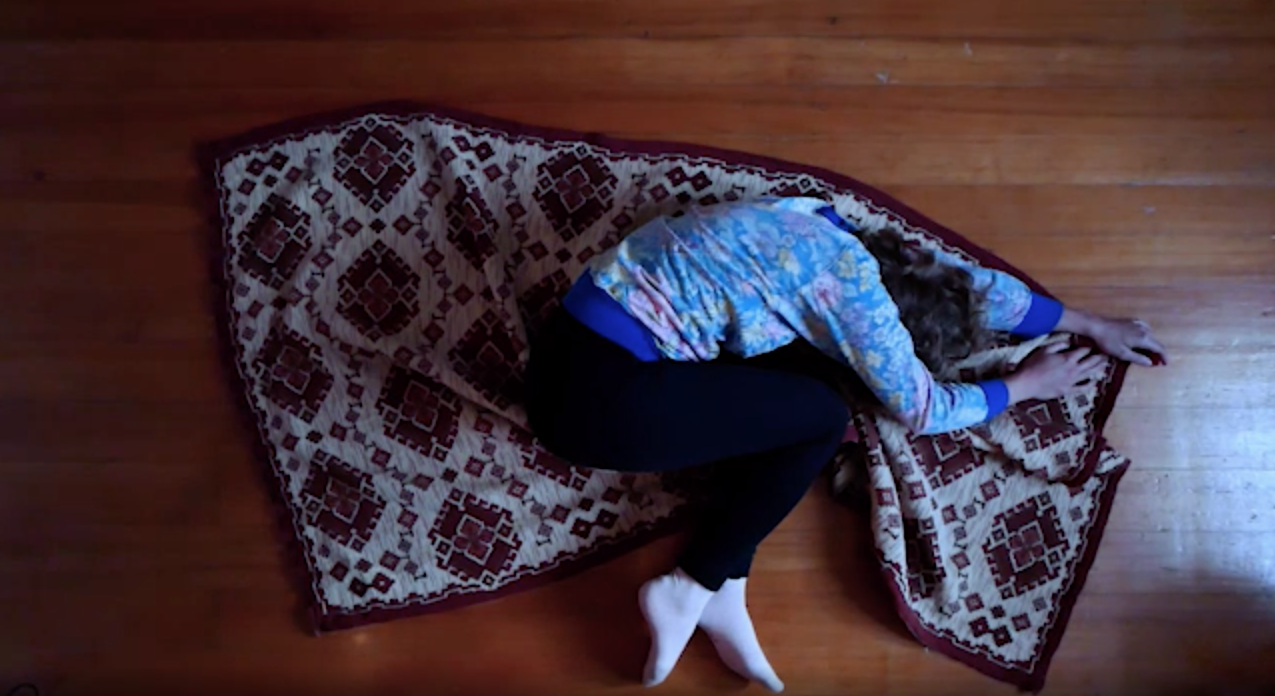The picture shows a person lying on a carpet and writhing on it.