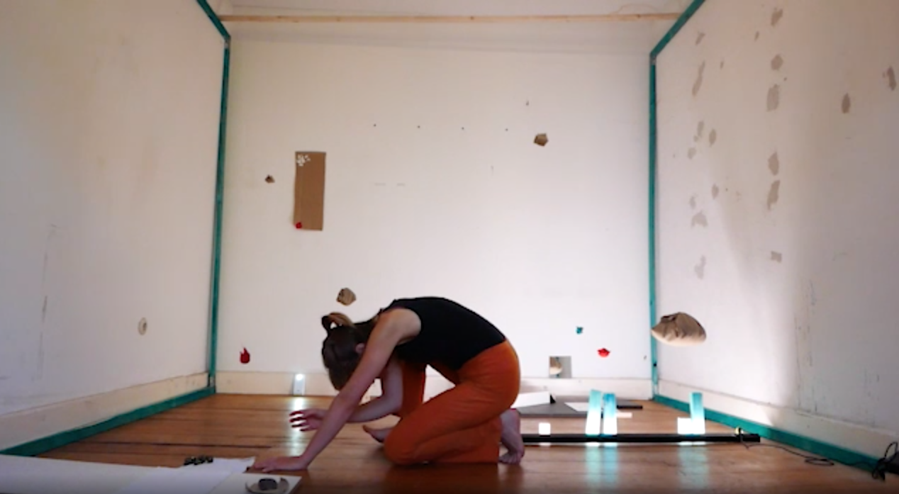 The image shows a person kneeling in a room full of objects.