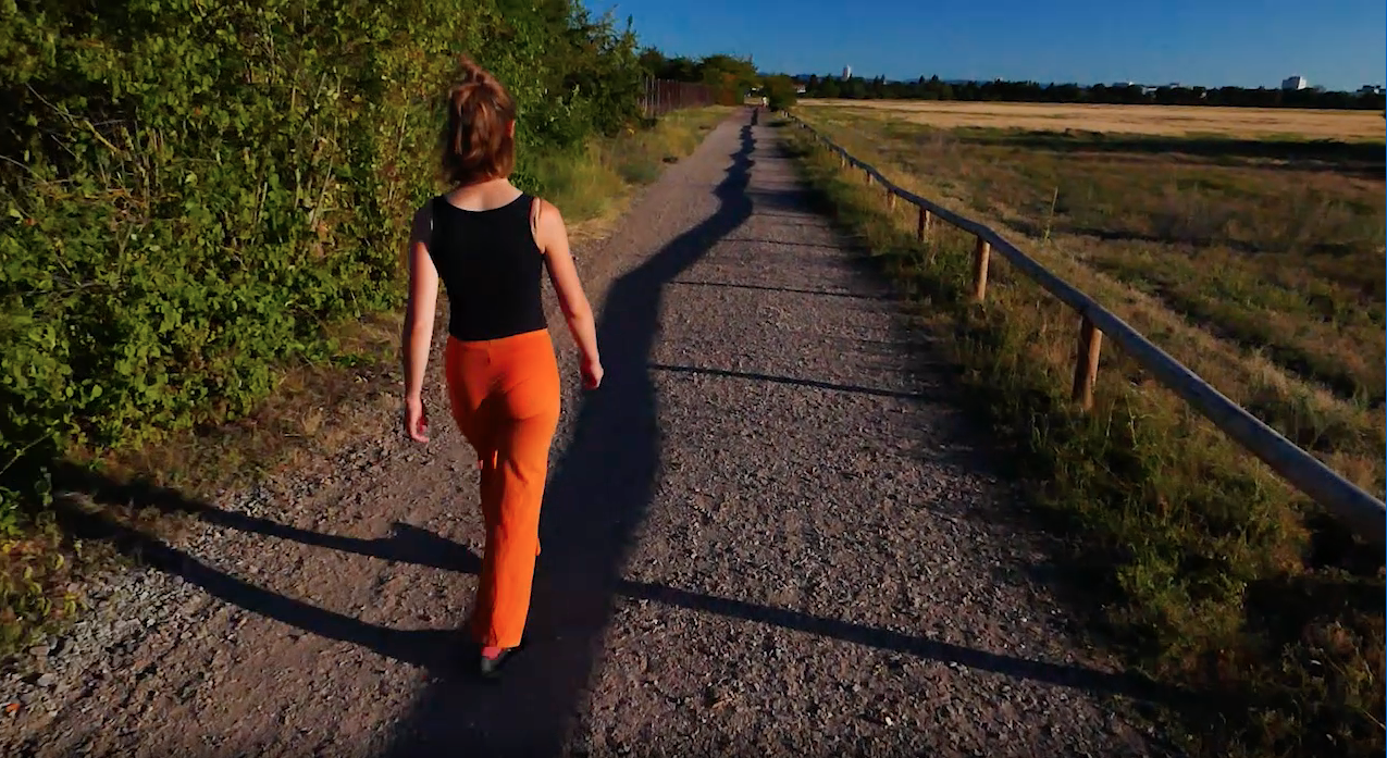The image shows a person walking along a shadow in the nature.