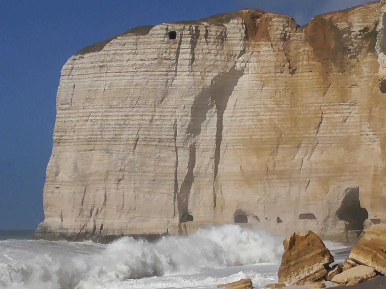 Ein enormer Felsen füllt fast das ganze Bild aus. An seinem Fuß branden kräftig die Wellen, an seiner Spitze zieht sich wolkenloser Sommerhimmel.