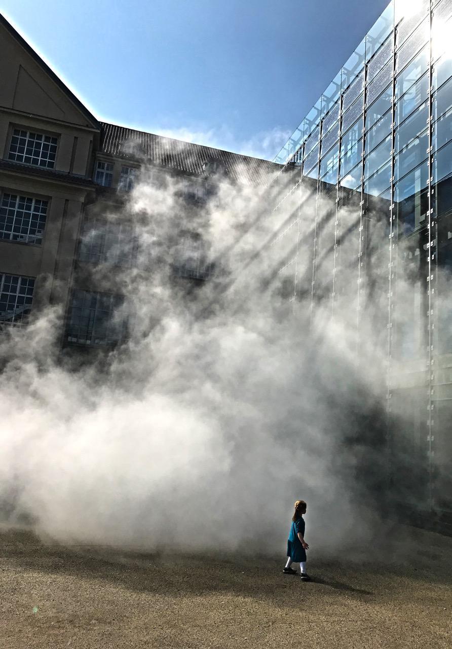 Eine Skulptur aus Nebel umschließt ein gläsernes Gebäude.