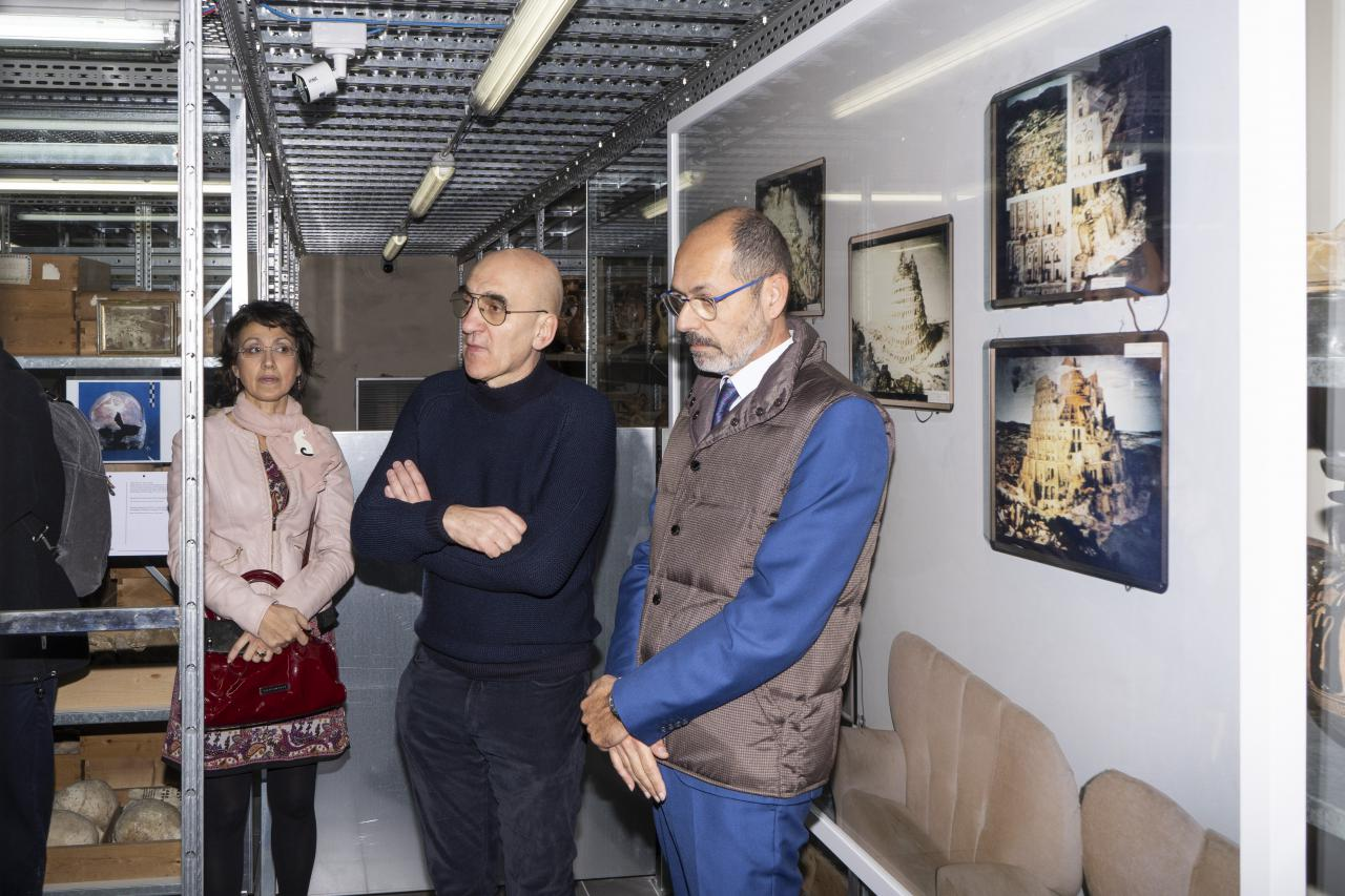 Three people are standing in a storage room with different objects.