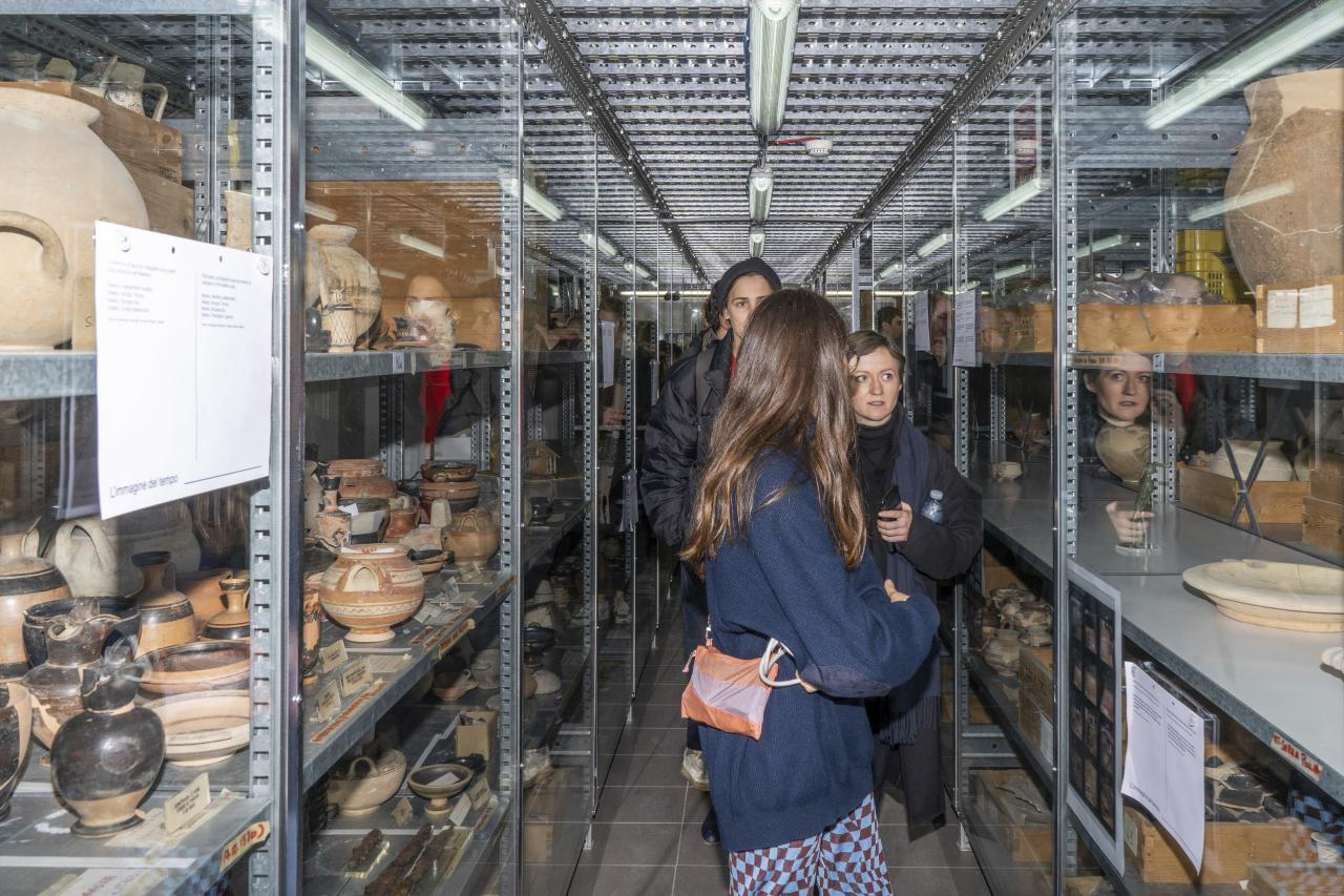 Three women stand in a storeroom with various objects.